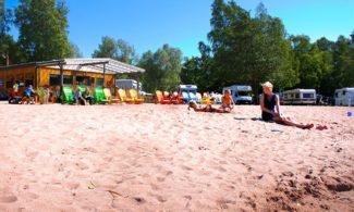 Poroholman rantatalo. Ihmisiä rantahiekalla ja iloisen värisiä rantatuoleja.