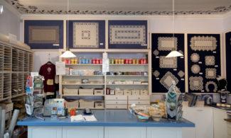 Pits-Priia myymälän seinällä nyplättyjä pitsiliinoja ja hyllyssä eri värisiä kynttilöitä ja muita matkamuistoja.