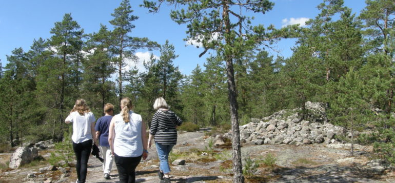 A group in Sammallahdenmäki with a guide