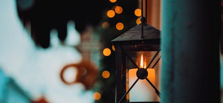 Musta lyhty ja jouluvalot taustalla.