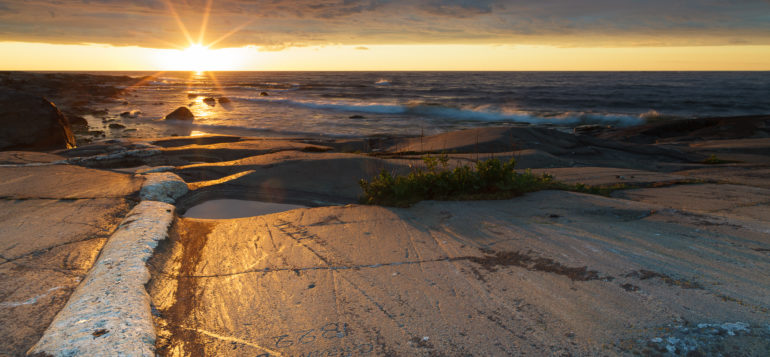 Sunset in Kylmäpihlaja. Waves are hitting the rocks.