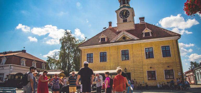 Vanhan Raatihuoneen edessä seisoo ihmisiä aurinkoisena kesäpäivänä.